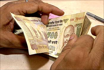 A cashier counts currency notes inside a bank.