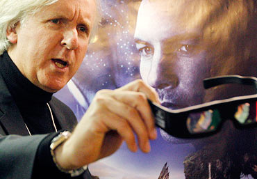 James Cameron shows 3D glasses as he poses in front of an Avatar poster