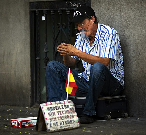 Manuel Sastre, 59, lights a cigarette as he asks for money in central Madrid.