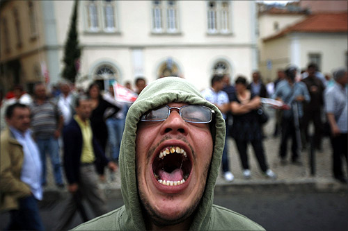 A demonstrator shouts slogans against the government during a protest opposite the Portuguese parliament in Lisbon.