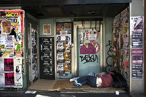Two people sleep outside a closed down business in Madrid.