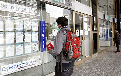 A man checks job offers outside a recruitment agency in downtown Milan.
