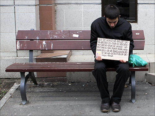 A man holds a banner as he sits on a bench in Bucharest.