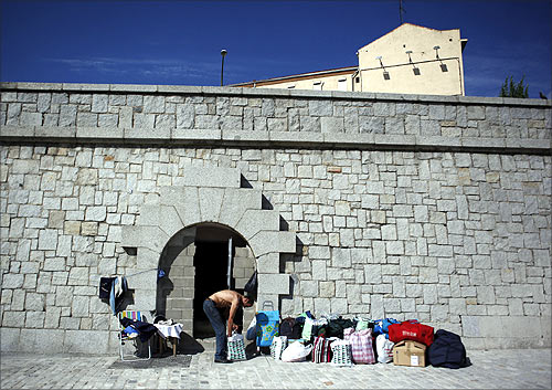 Paco, 59, pack his belongings as he is evicted from his home, a small opening on a wall adjacent to Madrid's Toledo bridge.