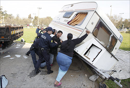 Mateus Silva, 25 and unemployed, and his wife Leonor, upturn their caravan while city police officers arrive to evict him in the Nossa Senhora de Fatima neighborhood.