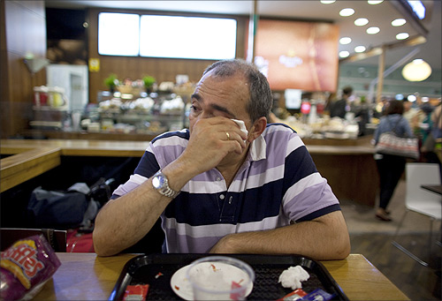 Jose Manuel Abel, 46, cries as he waits to catch a flight to Munich at El Prat airport in Barcelona.
