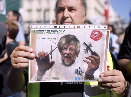 A civil service worker holds up a placard depicting a parody of Spain's Prime Minister Mariano Rajoy during a protest over government austerity measures.