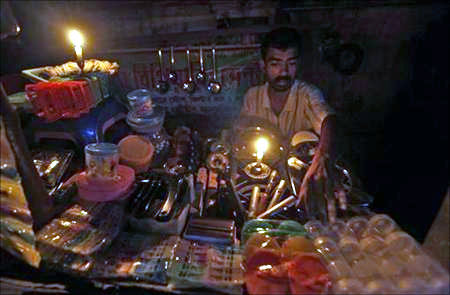 A gas oven mechanic waits for customers in his shop during a power-cut in Kolkata.