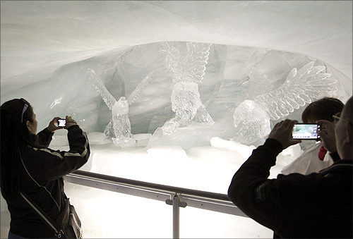 Tourists take pictures of ice sculptures in the Ice Palace glacier cave at the Jungfraujoch.