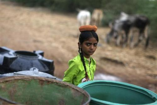 A girl stands next to the empty containers after the government-run water tanker left at Charanka village in Gujarat.