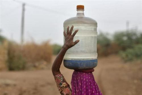 A village woman carries a container filled with drinking water supplied by the government-run water tanker at Charanka village in Gujarat.