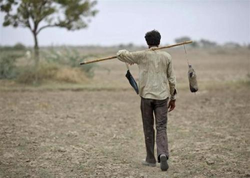 A villager carries a water bottle as he heads towards his cattle on the outskirts of Sami town in Gujarat.