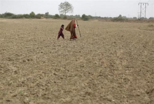 A woman walks with a boy as they migrate due to lack of water at Sami village in Gujarat.