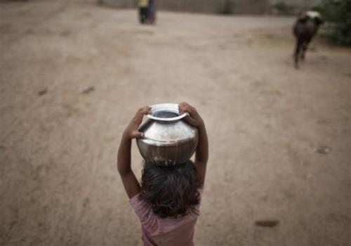 Five-year-old Joshiya, carries a metal pitcher filled with water from a near-by well at Badarganj village in Gujarat.