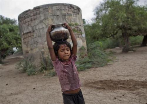 Five-year-old Joshiya carries a metal pitcher filled with water from a near-by well at Badarganj village in Gujarat.