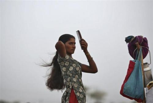 A village woman combs her hair after she migrated due to shortage of water on the outskirts of Sami town in Gujarat.