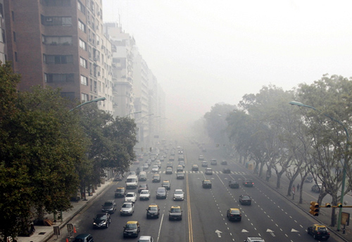 Cars drive through Del Libertador avenue amidst foggy conditions in downtown Buenos Aires.