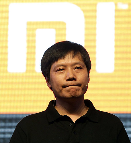 Lei Jun, founder and CEO of China's mobile company Xiaomi, pauses in front of his company's logo at a launch ceremony of Xiaomi Phone 2 in Beijing.