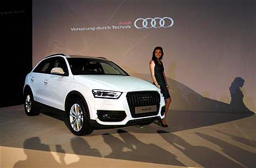 A model stands near a new Audi Q3 during its launch in Jakarta.