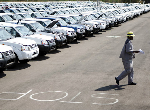 A worker walks near a row of cars at Nissan's manufacturing plant in Rosslyn, outside Pretoria, South Africa.
