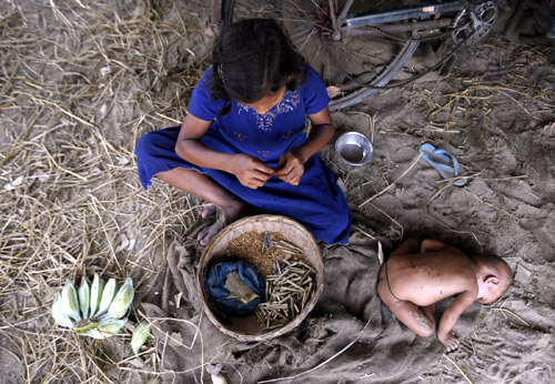 Ten-year-old labourer Toslima Khatun makes bidis (shredded tobacco hand-rolled in tendu leaves) as her seven-month-old sister Hasnuhana rests in Bhulki village.