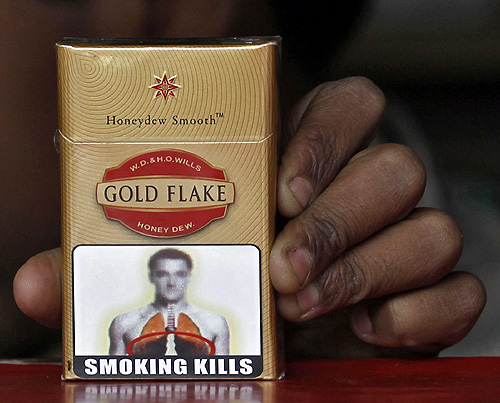 A vendor holds a cigarette pack printed with a picture bearing likeness to Chelsea's soccer player John Terry at his roadside stall in New Delhi.