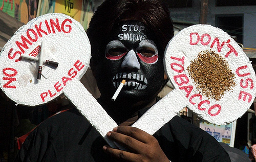 A man holds placards during an anti-tobacco awareness campaign.