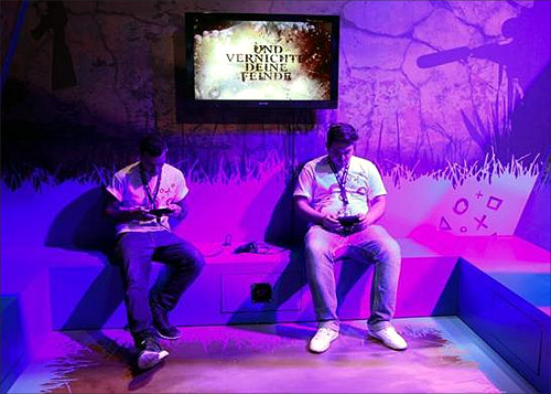 Visitors play Playstations at an exhibition stand during the Gamescom 2012 fair in Cologne.