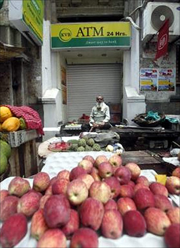 A roadside vendor selling fruits sits in front of a closed ATM counter during a two-day strike in Kolkata.