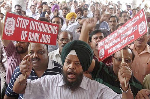 A bank employee shouts slogans while holding placards at a rally during a two-day strike in Chandigarh.