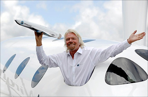 Richard Branson waves a model of the LauncherOne cargo spacecraft from a window of an actual size model of SpaceShipTwo on display.