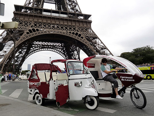 A velo taxi (R), or bicycle taxi, drives past the Eiffel Tower in Paris.