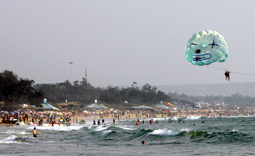 Tourists fly a paraglider over Baga beach in Goa.