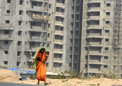 A woman carrying a child walks past a construction site for a commercial building on the outskirts of the southern Indian city of Hyderabad.
