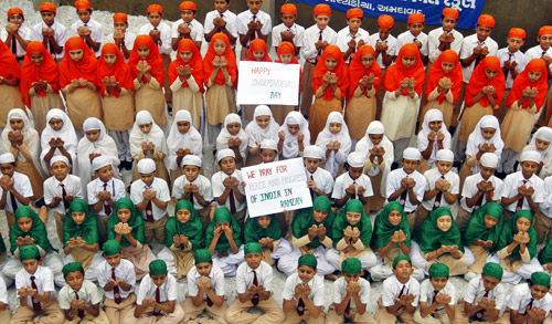 School children dressed in tri-colours of India's national flag, offer prayers on the eve of the country's Independence Day celebrations in Ahmedabad.
