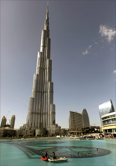 Workers move on a boat in an artificial lake at Dubai Mall in front of the Burj Khalifa.