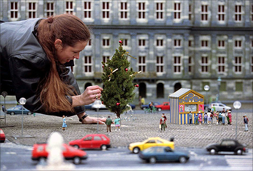 A worker at the miniature city of Madurodam decorates a Christmas tree with in the surroundings of the Royal palace on the Dam in Amsterdam.