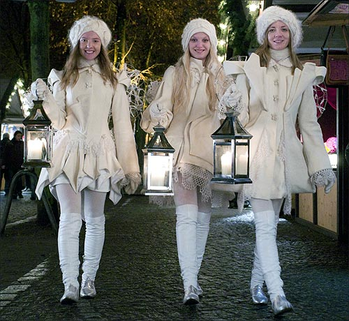 Girls dressed as angels walk through a Christmas market at the Charlottenburg castle in Berlin.