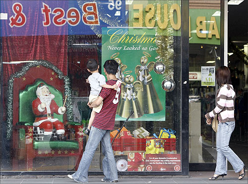 A family walk past a Christmas window display at a department store in suburban Melbourne.