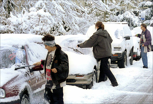 Residents remove snow from their cars after heavy snowfalls in Zurich.