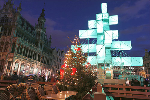 A traditional Christmas tree (front C) is seen near an illuminated steel installation at Brussels' Grand Place.
