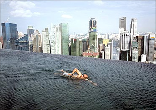 A guest swims in the infinity pool of the Skypark that tops the Marina Bay Sands hotel towers.