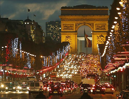 Christmas holiday lights hang from trees to illuminate Champs Elysees in Paris as rush hour traffic fills the avenue leading up to the Arc de Triomphe.
