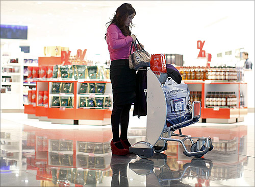 A woman from China stands with a shopping trolley in front of a Duty Free store at the Fraport airport in Frankfurt.