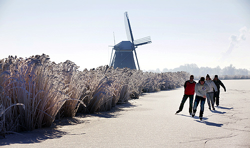 Four skaters pass a windmill as they enjoy the first time they can skate on natural ice in Zevenhuizen, near The Hague.