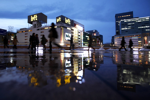 Pedestrians are reflected in a puddle in front of Sendai train station, Miyagi prefecture, northeastern Japan.