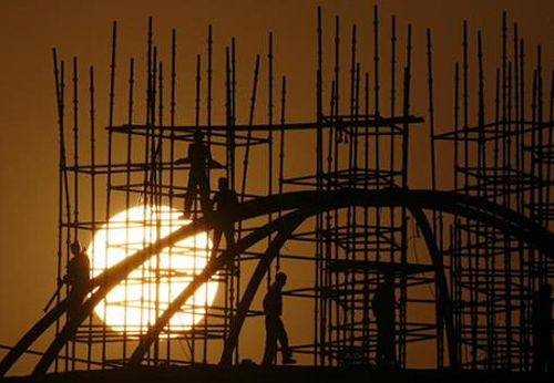 Labourers working at a construction site as sun sets in New Delhi.