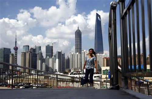 A woman walks on a bridge near the Pudong Lujiazui financial area in Shanghai.