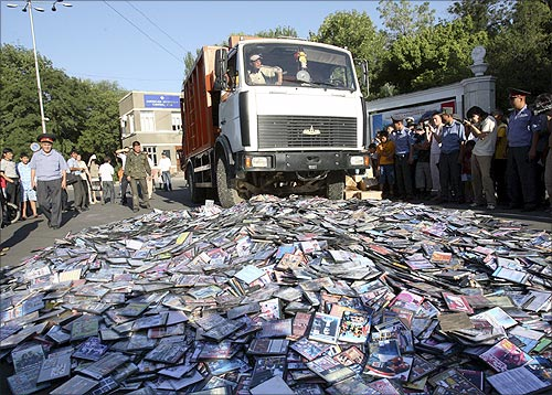 A truck crushes a pile of pirated CDs and DVDs.