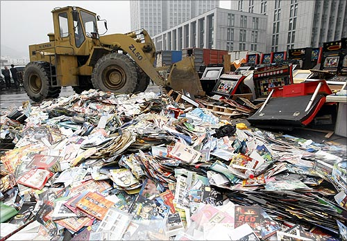 An excavator destroys confiscated pirated publications and illegal video game machines during a campaign against piracy in Hangzhou.